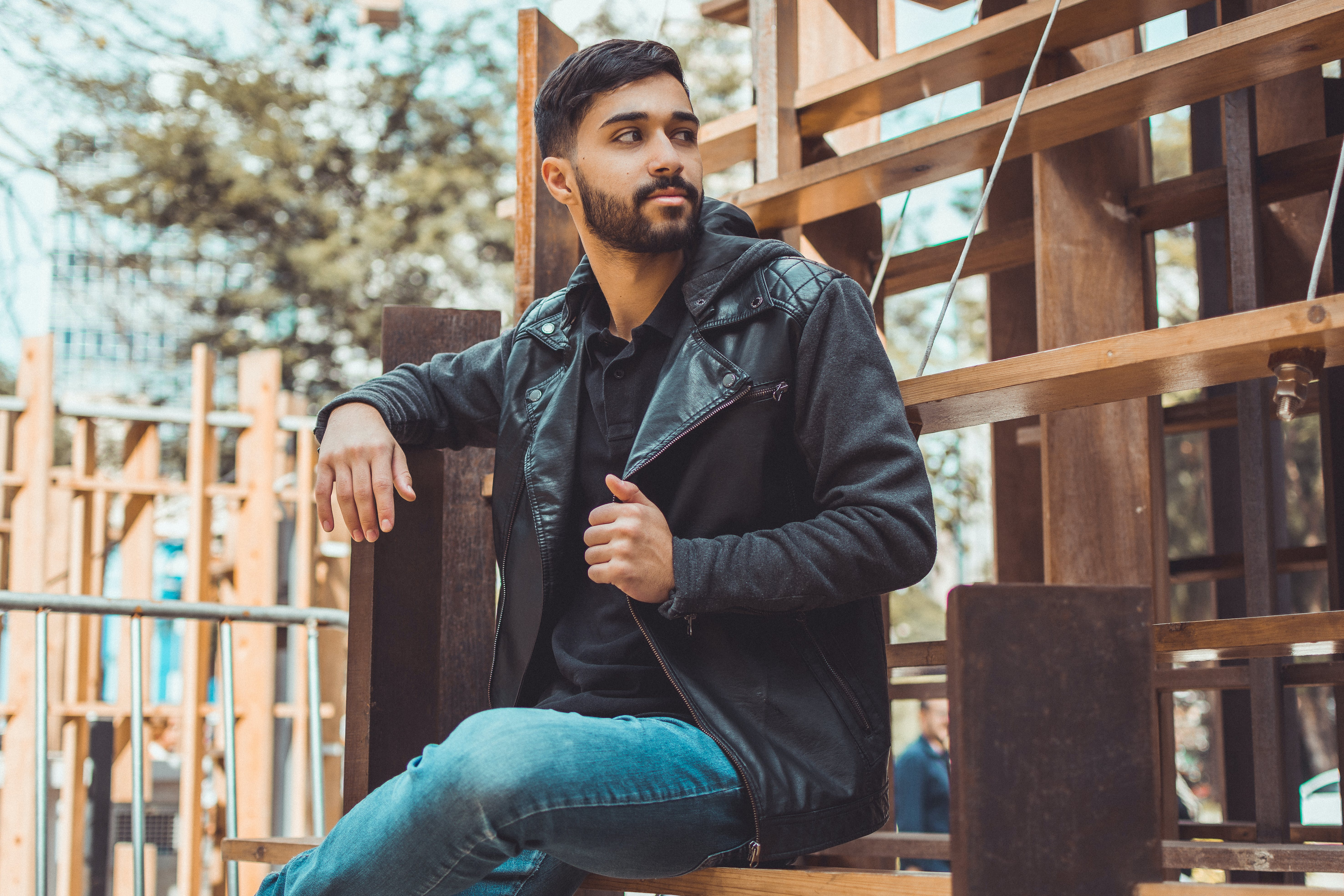 Man Wearing Black Jacket and Jeans Sitting on Brown Wooden Chair