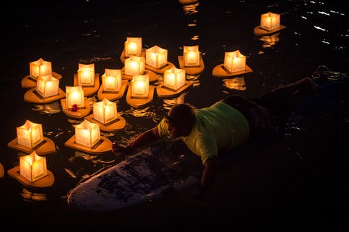 Man Rides on Surfboard Near Paper Lanterns on Body of Water during Nighttime