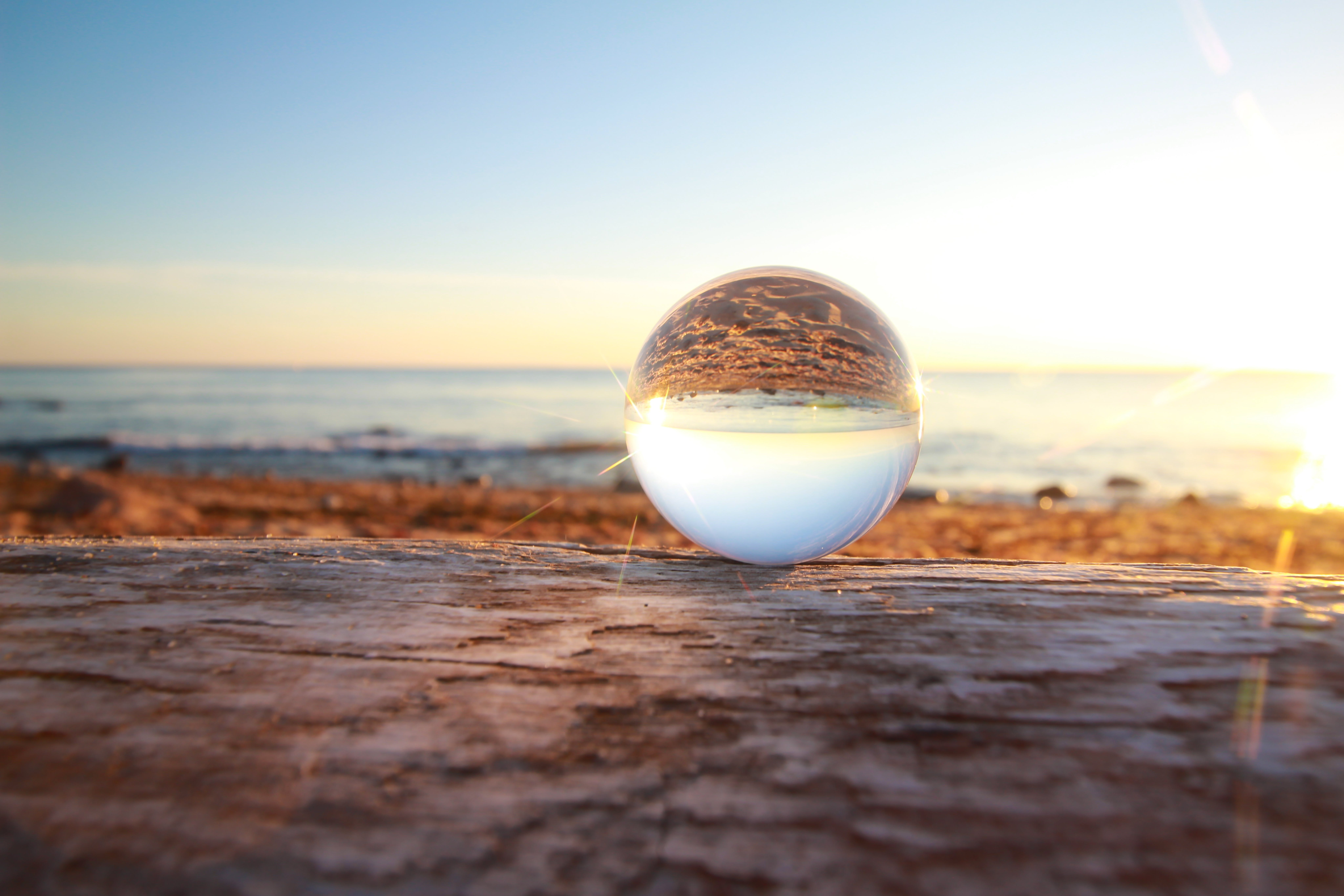 Clear Marble Toy Reflecting Seashore during Golden Hour