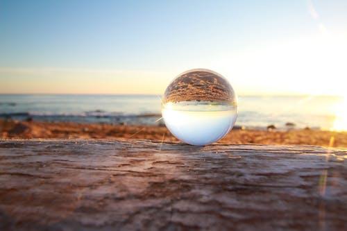 Foto profissional grátis de água, areia, beira-mar, bola de cristal