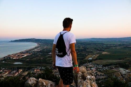Man Wearing Drawstring Bag Standing On Top Of Mountain