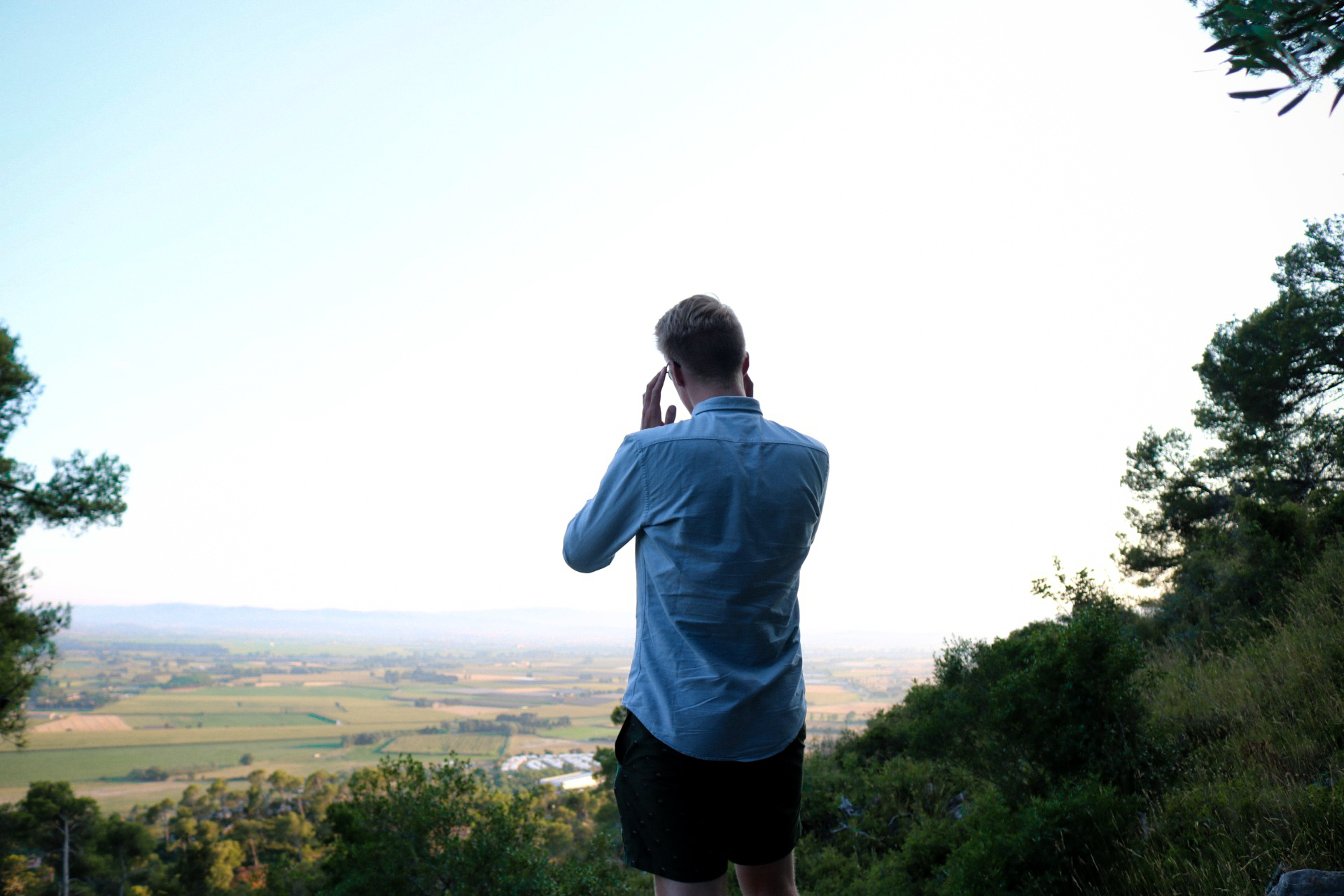 Man in Blue Dress Shirt Standing in Front of Landscape