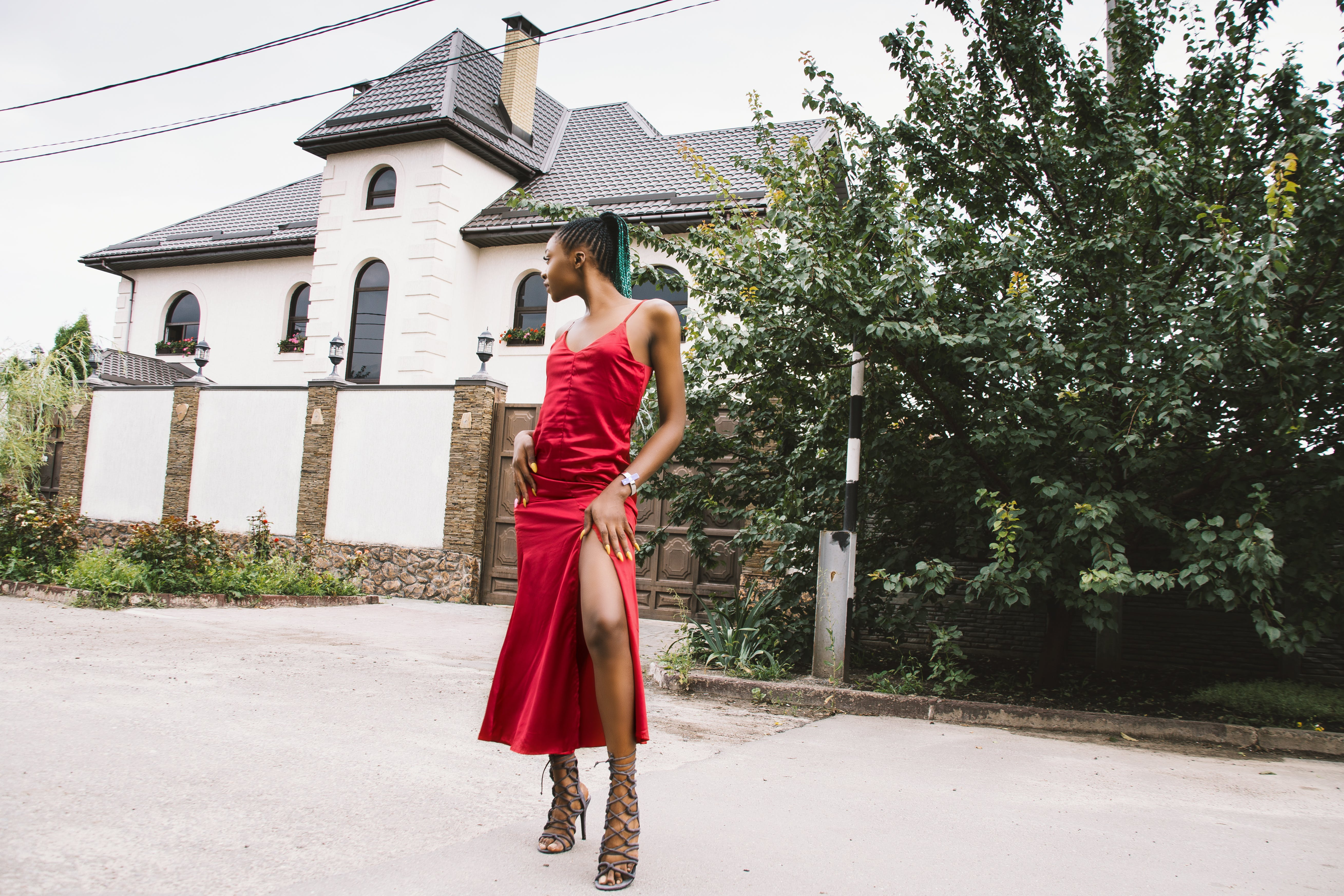 Woman Wearing Red Spaghetti Strap Split Dress in Front of White and Gray House