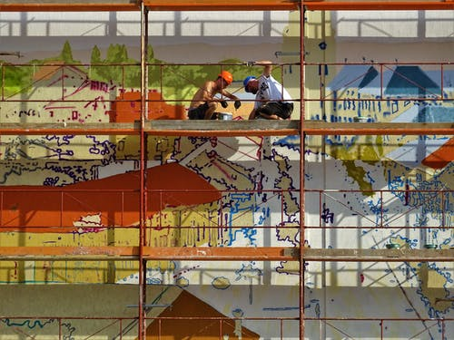 Two Person on Scaffolding Painting Wall