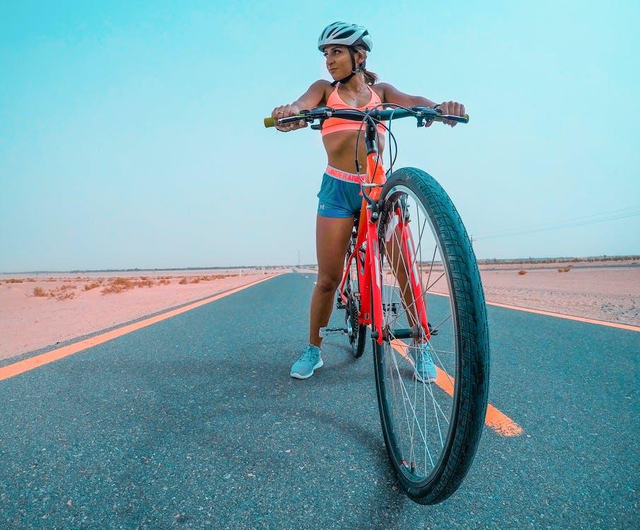 Woman Riding Red Mountain Bike On Asphalt Road