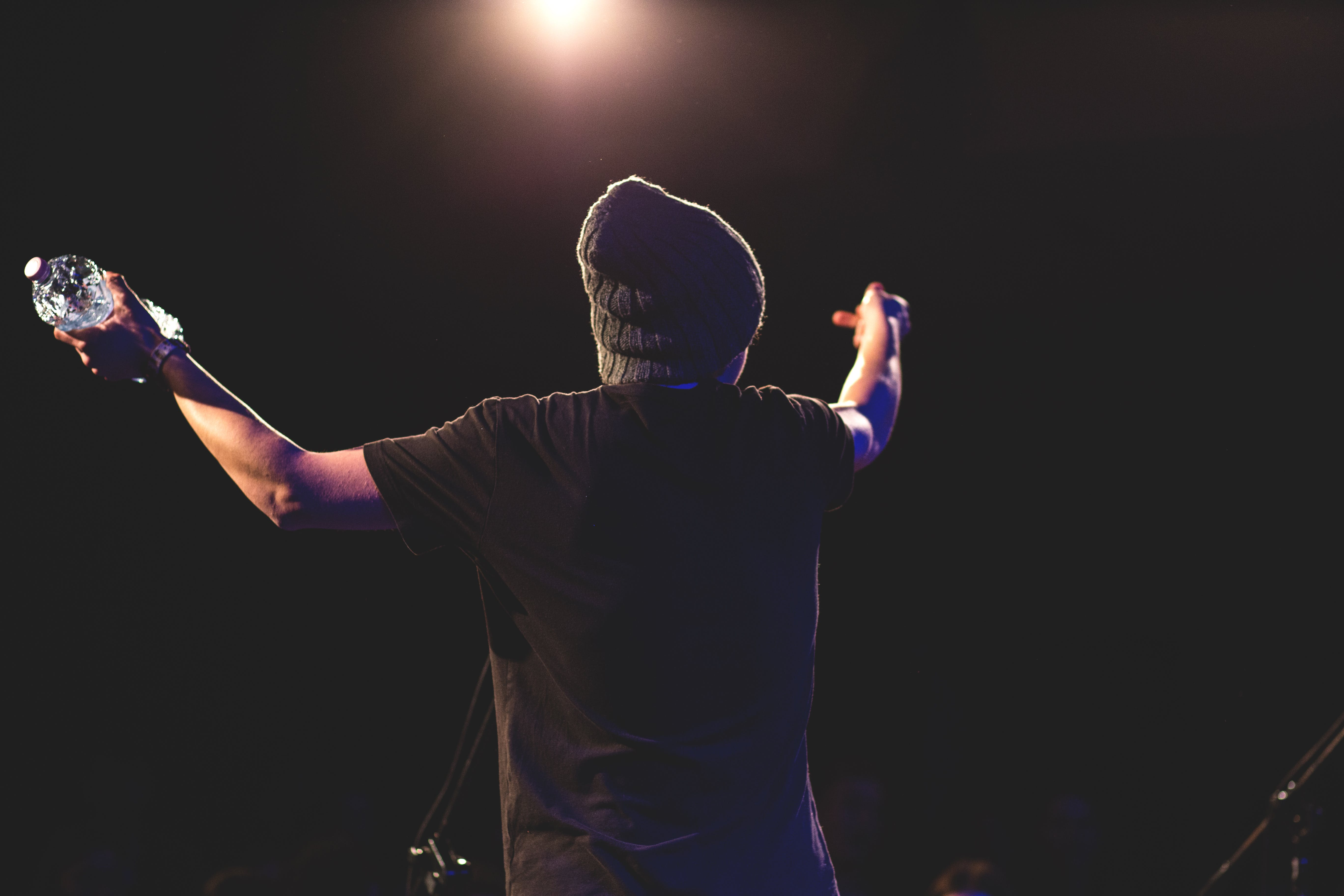 Man in Black T Shirt Standing While Spreading His Arms Facing Light