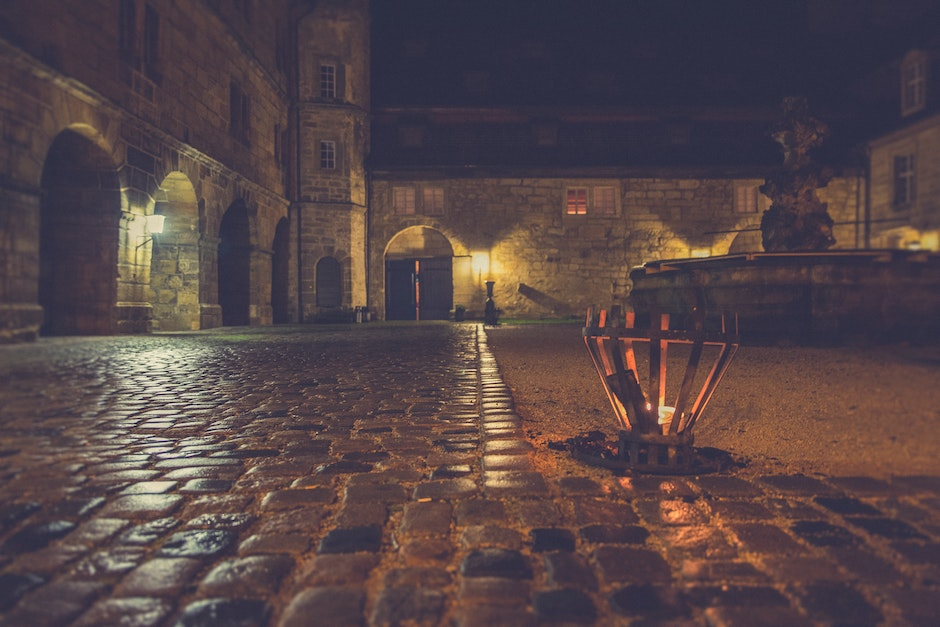 Brown Outdoor Lamp Beside Gray Stone Pavement during Nighttime