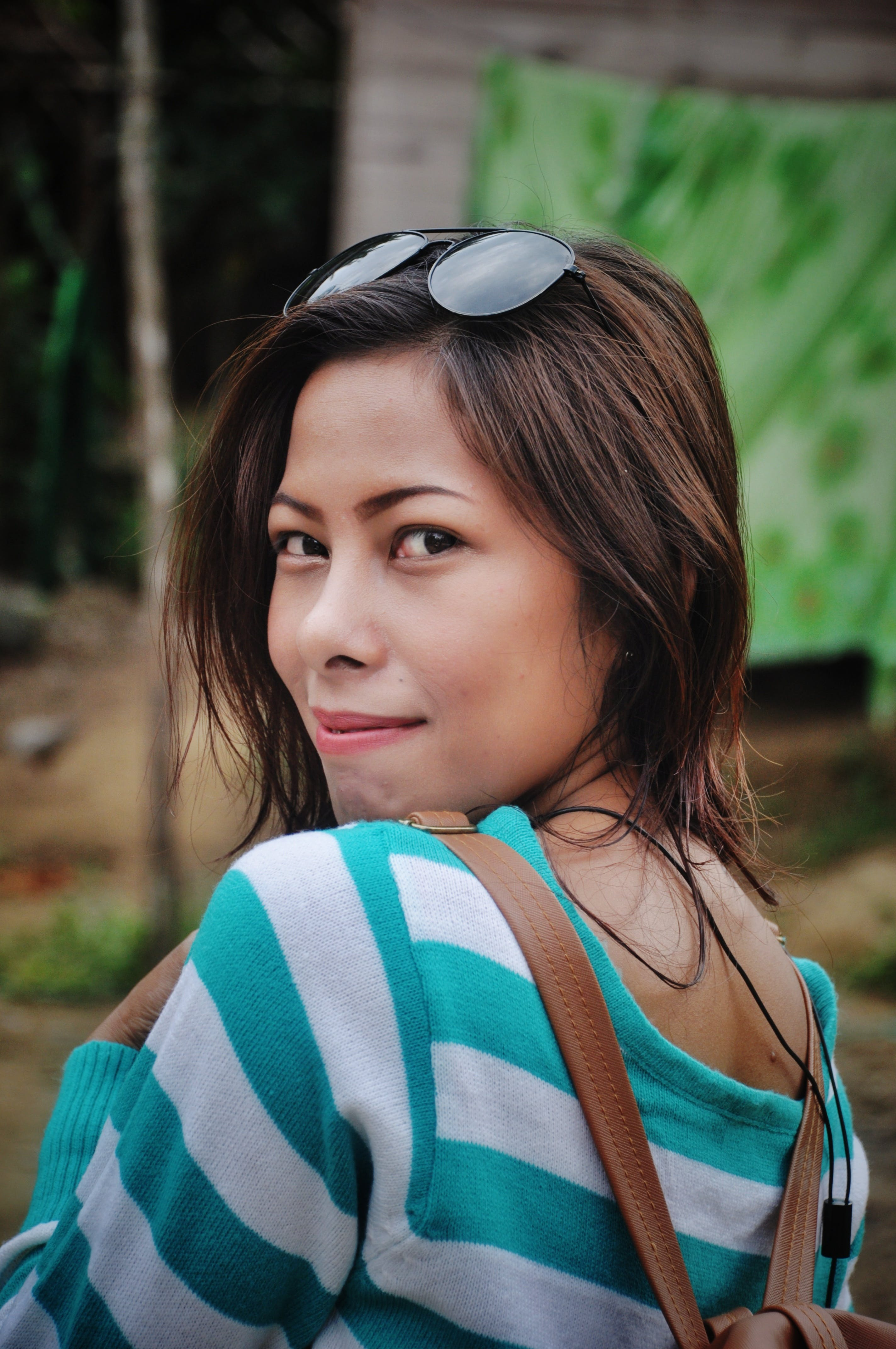 Shallow Depth of Field Photography of Woman in White and Teal Striped Long-sleeved Shirt With Sunglasses