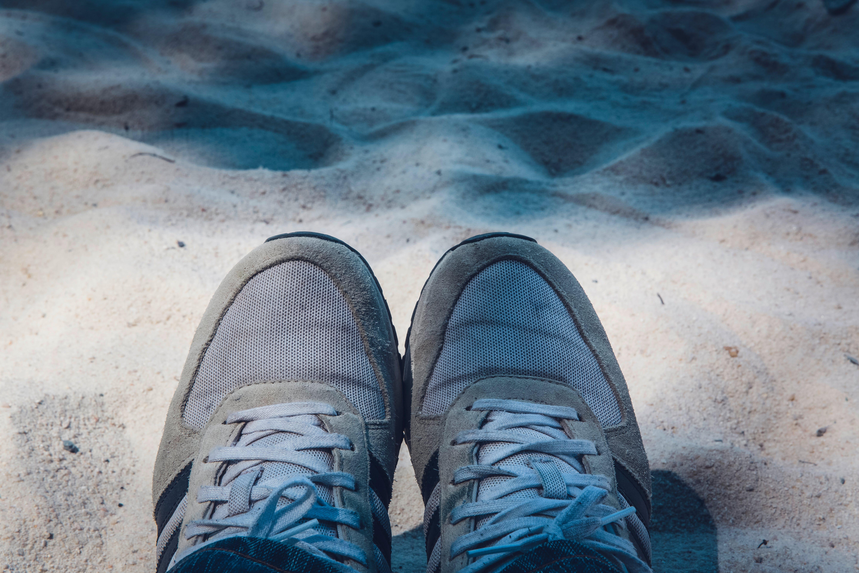 Kostenloses Stock Foto zu fußbekleidung, füße, sand, sneakers