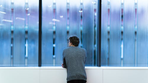 Man Standing and Facing on Glass Wall