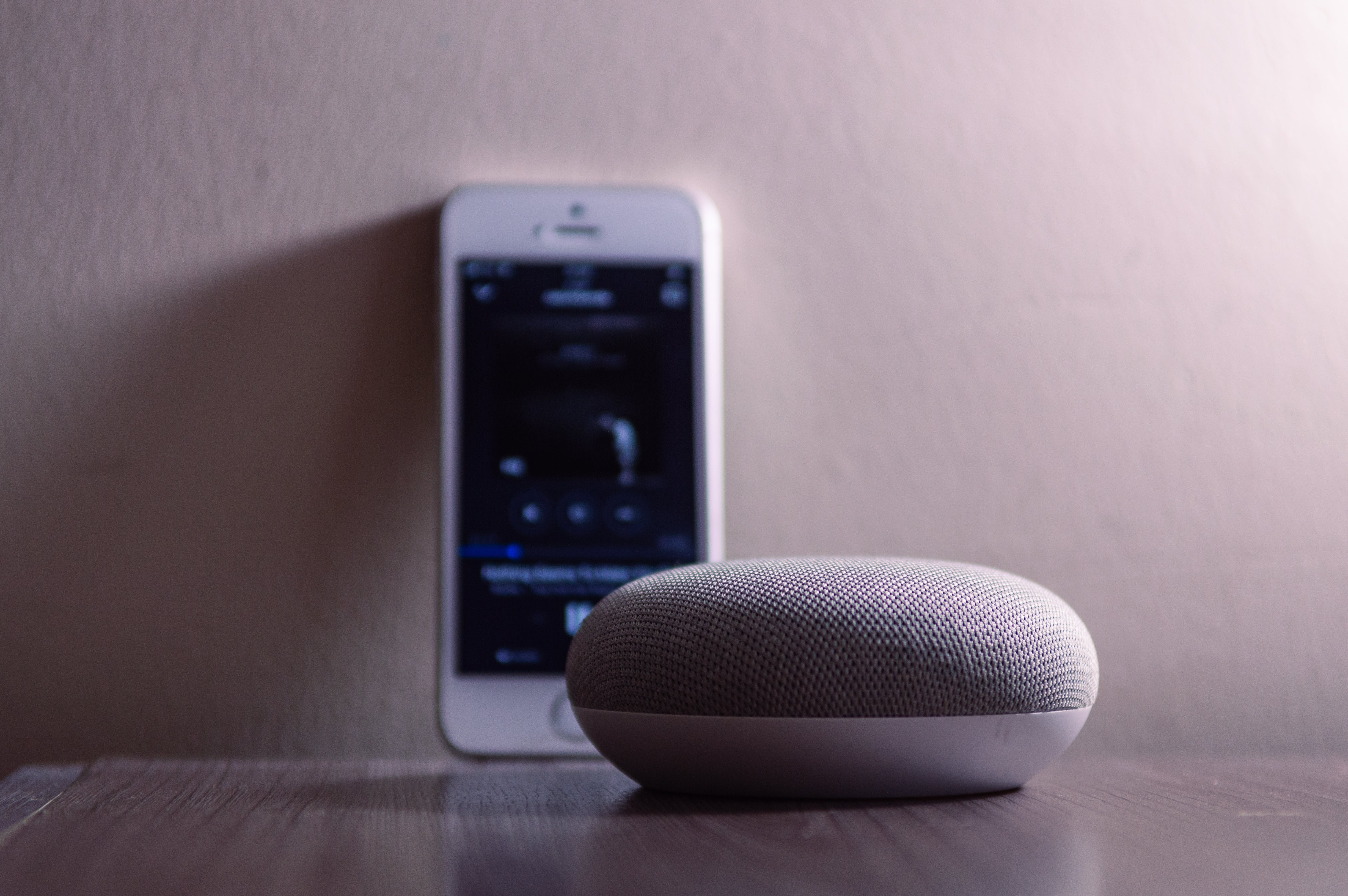Gray Google Home Mini Beside Silver Iphone 5s
