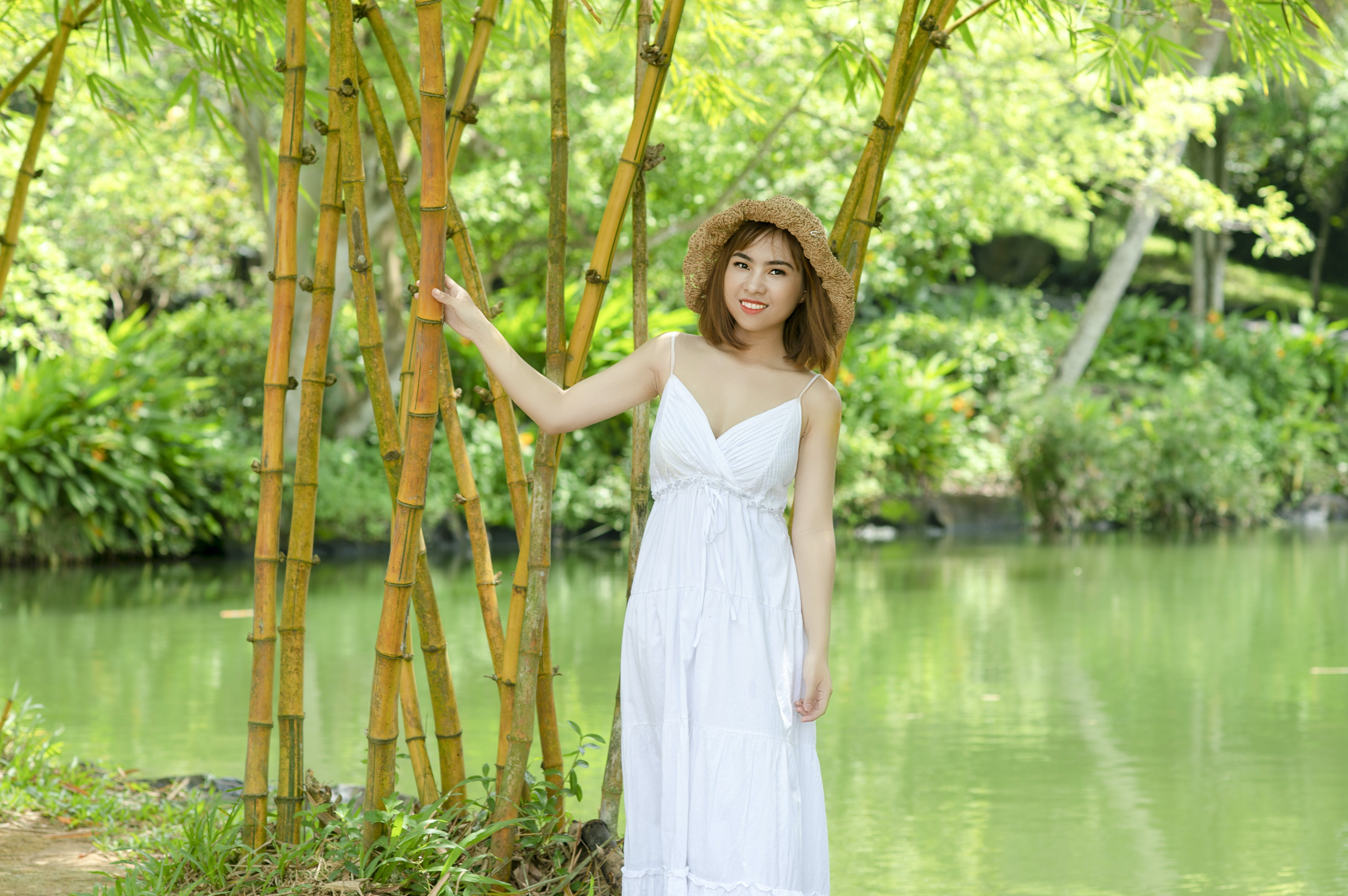 Woman in White Spaghetti Strap Dress Holding on Bamboo Tree Near Body of Water