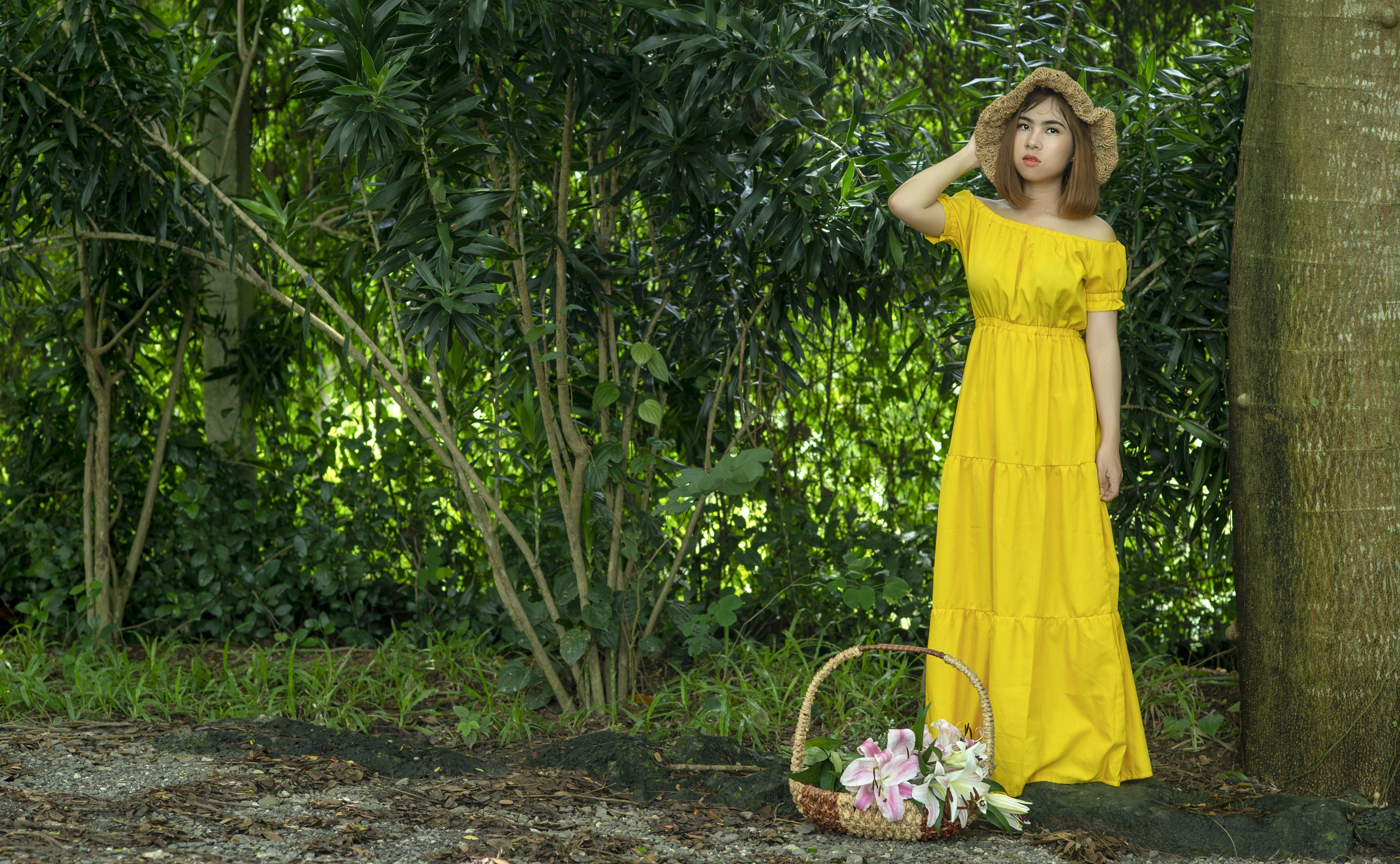 Woman Wearing Yellow Dress Beside Basket With Flowers