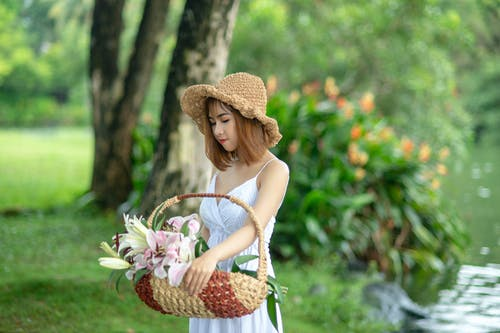 Photo of Women Carrying Basket With Pink Petal Flower