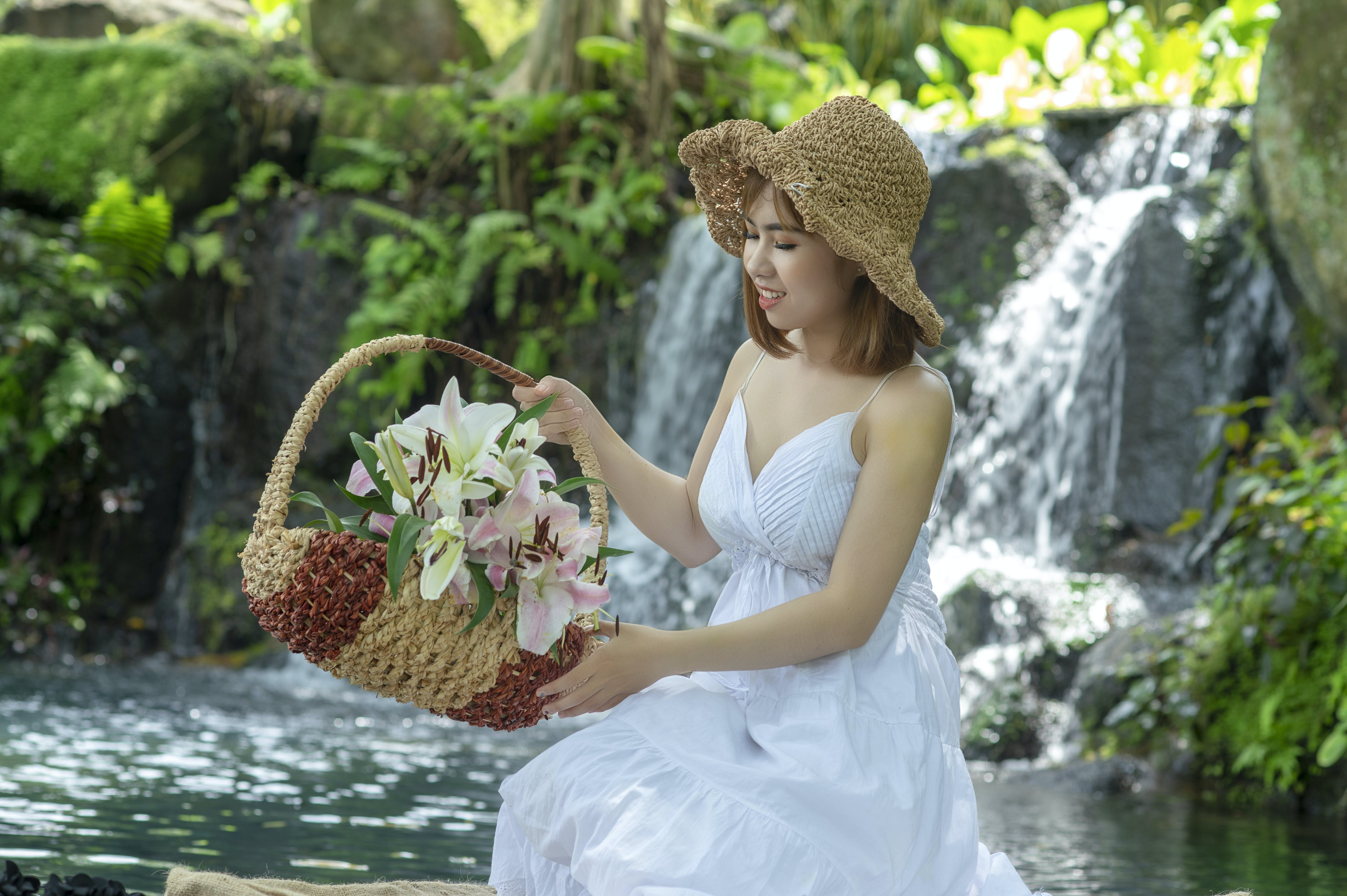 Woman Holding Basket While Sitting Near Waterfall