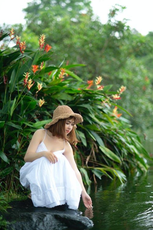 Woman Wearing White Dress Squatting Near Body of Water Near Plants