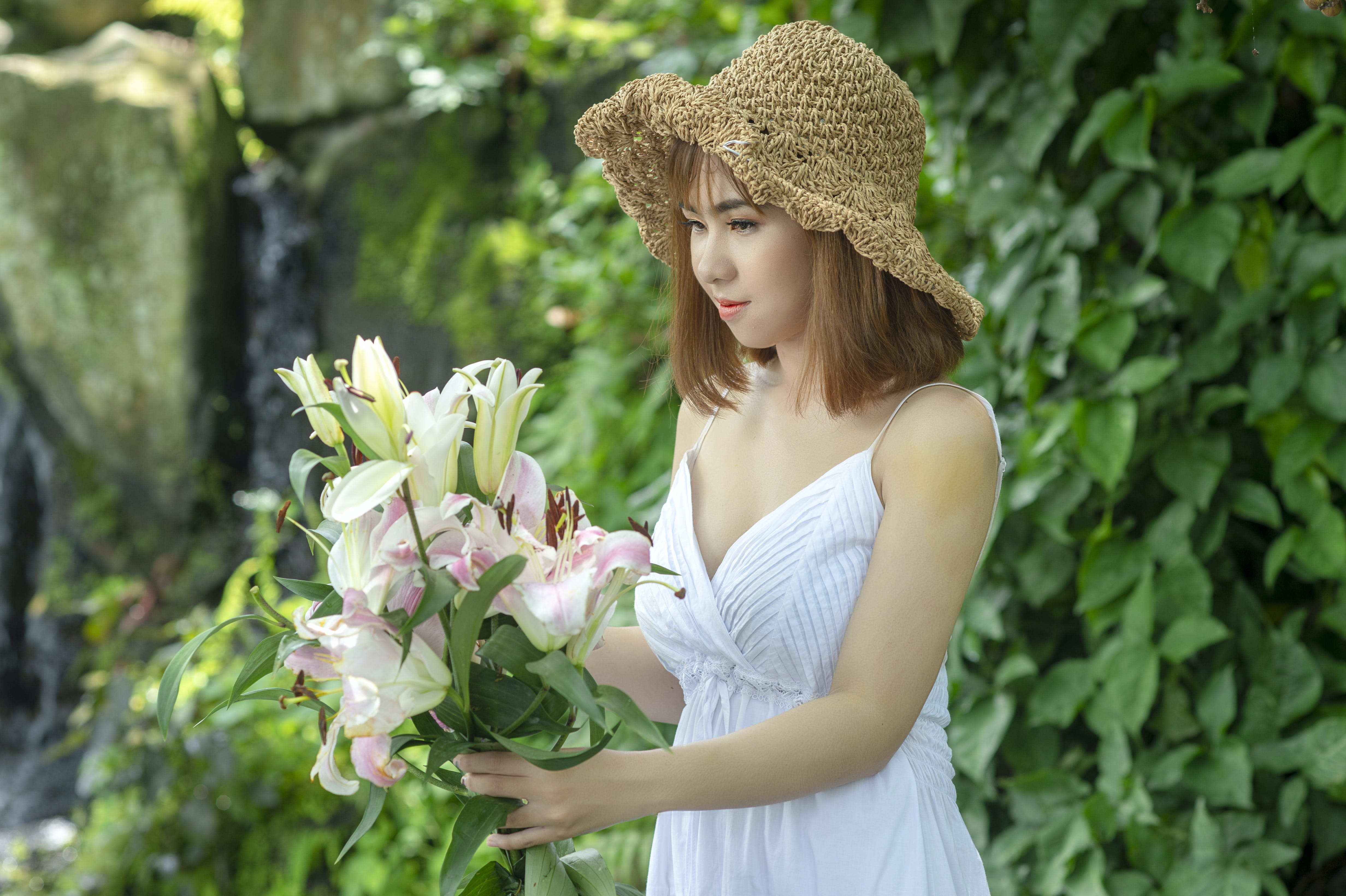 Woman Holding White and Pink Lily Flowers Near Green Leafed Plants