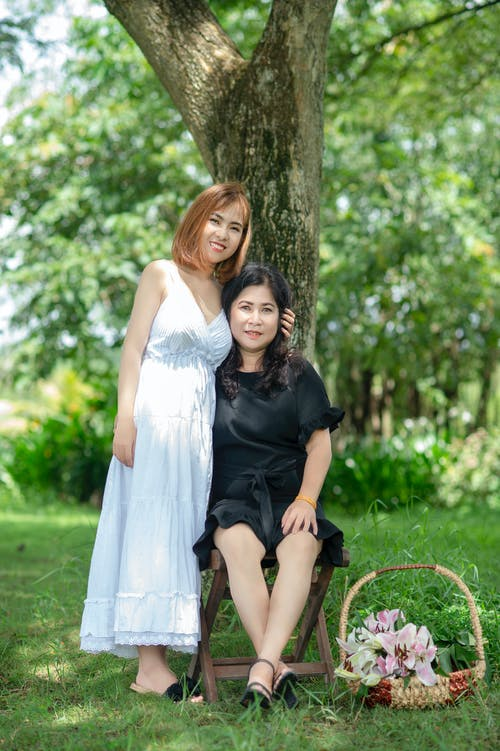Smiling Woman Standing Beside Smiling Woman Sitting on Folding Stool Under Tree