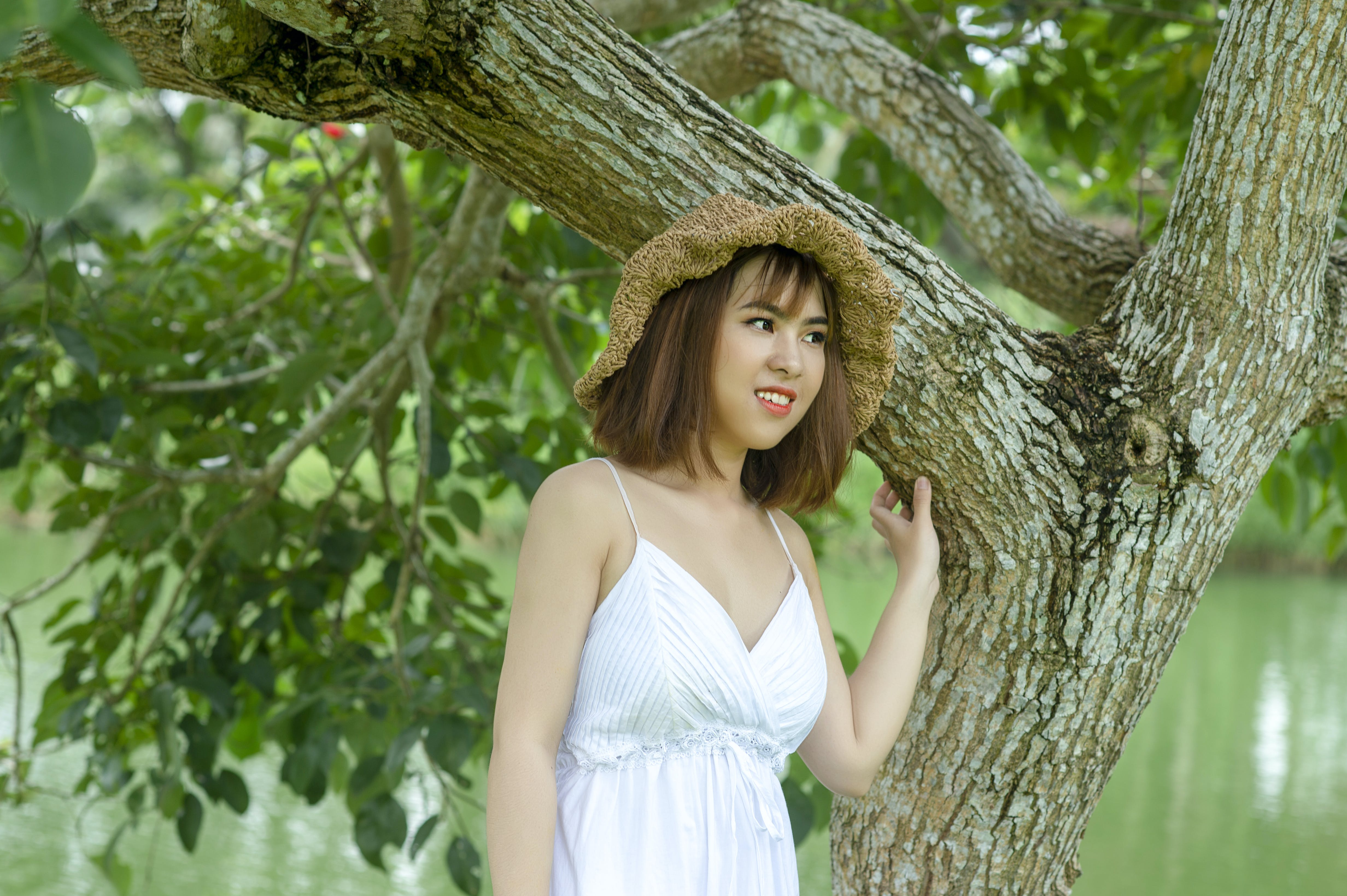 Woman Wearing Brown Hat Standing Under Green Tree