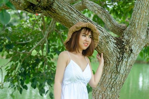 Woman Wearing Brown Hat Standing Under Green Tree