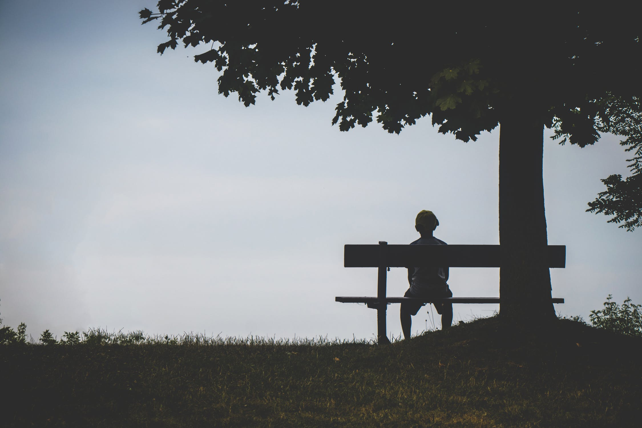 The silhouette of a person sitting on a park bench alone