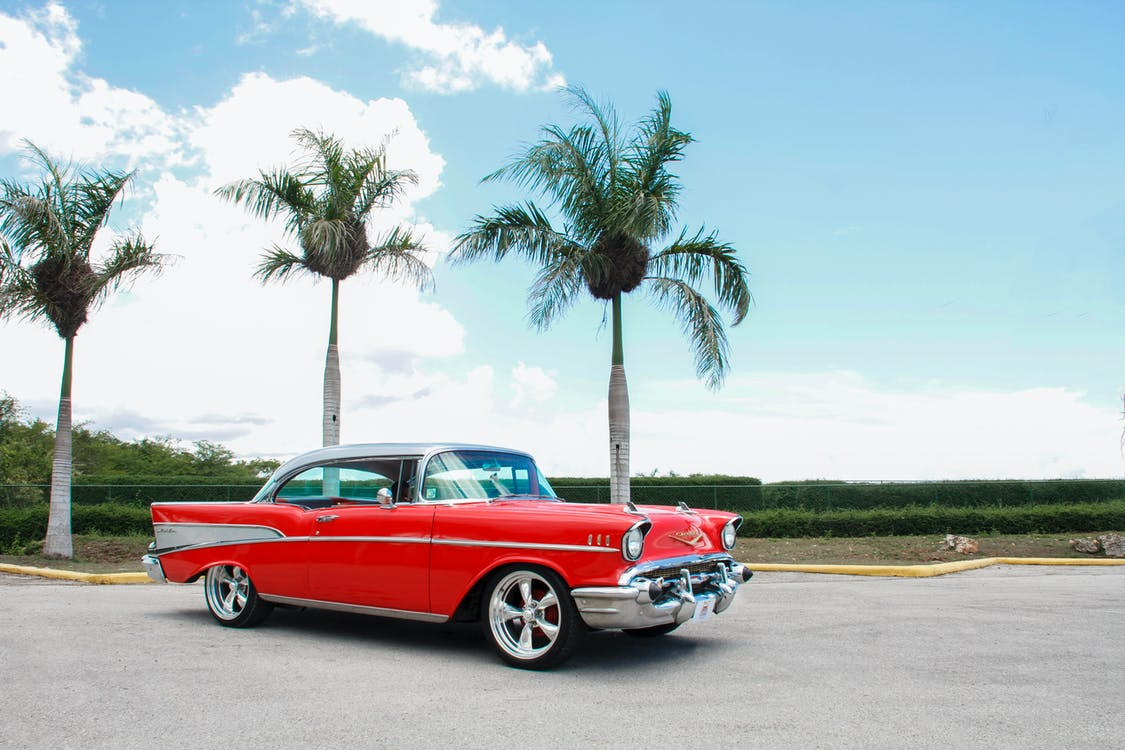 Red Coupe Near Trees Under White Clouds