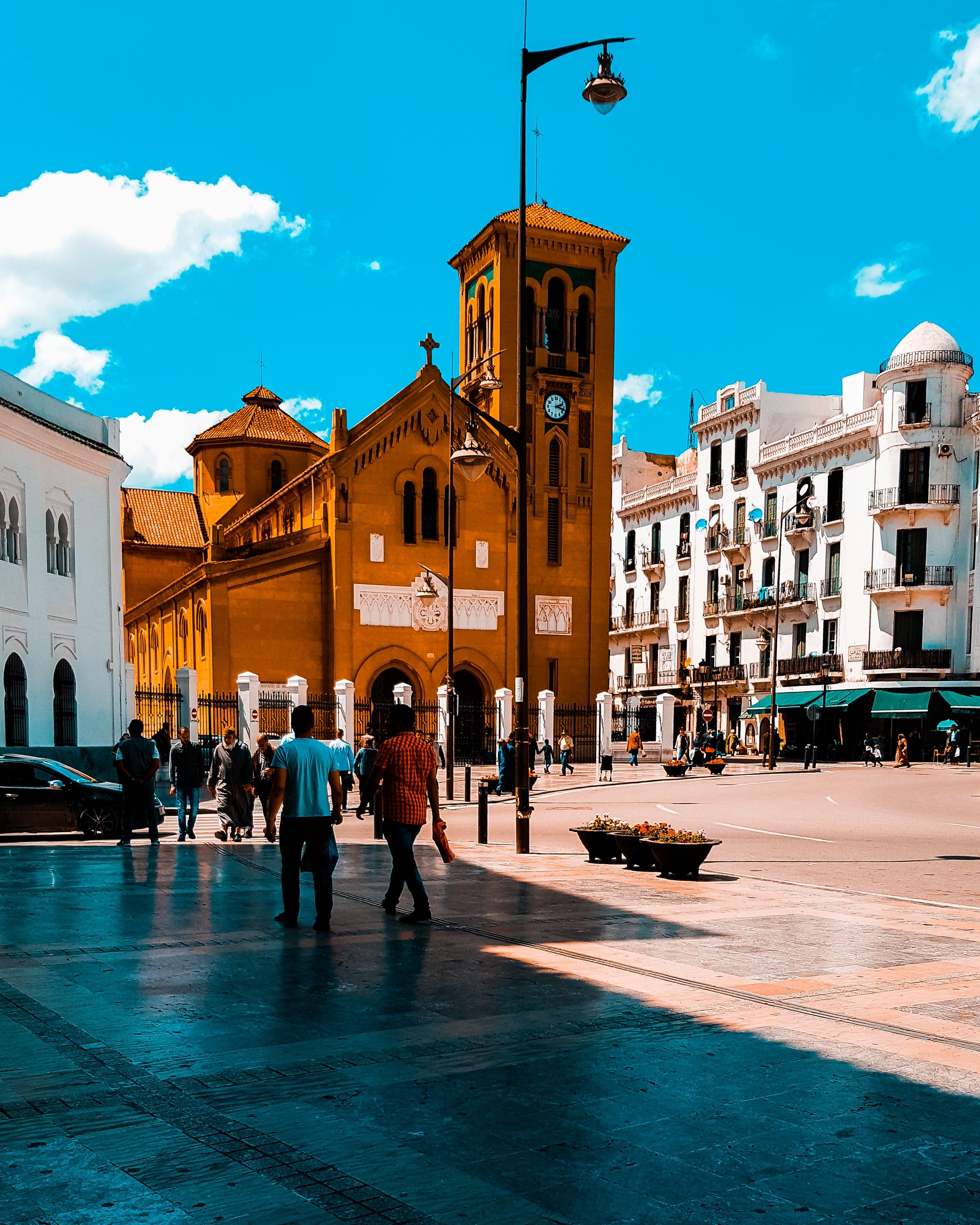 People Walking on Sidewalk Near Brown Cathedral