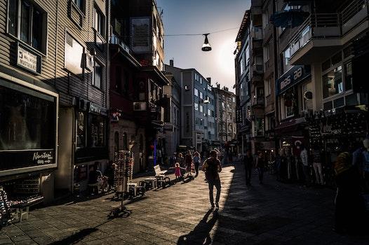 People Walking on Street Between High Rise Building