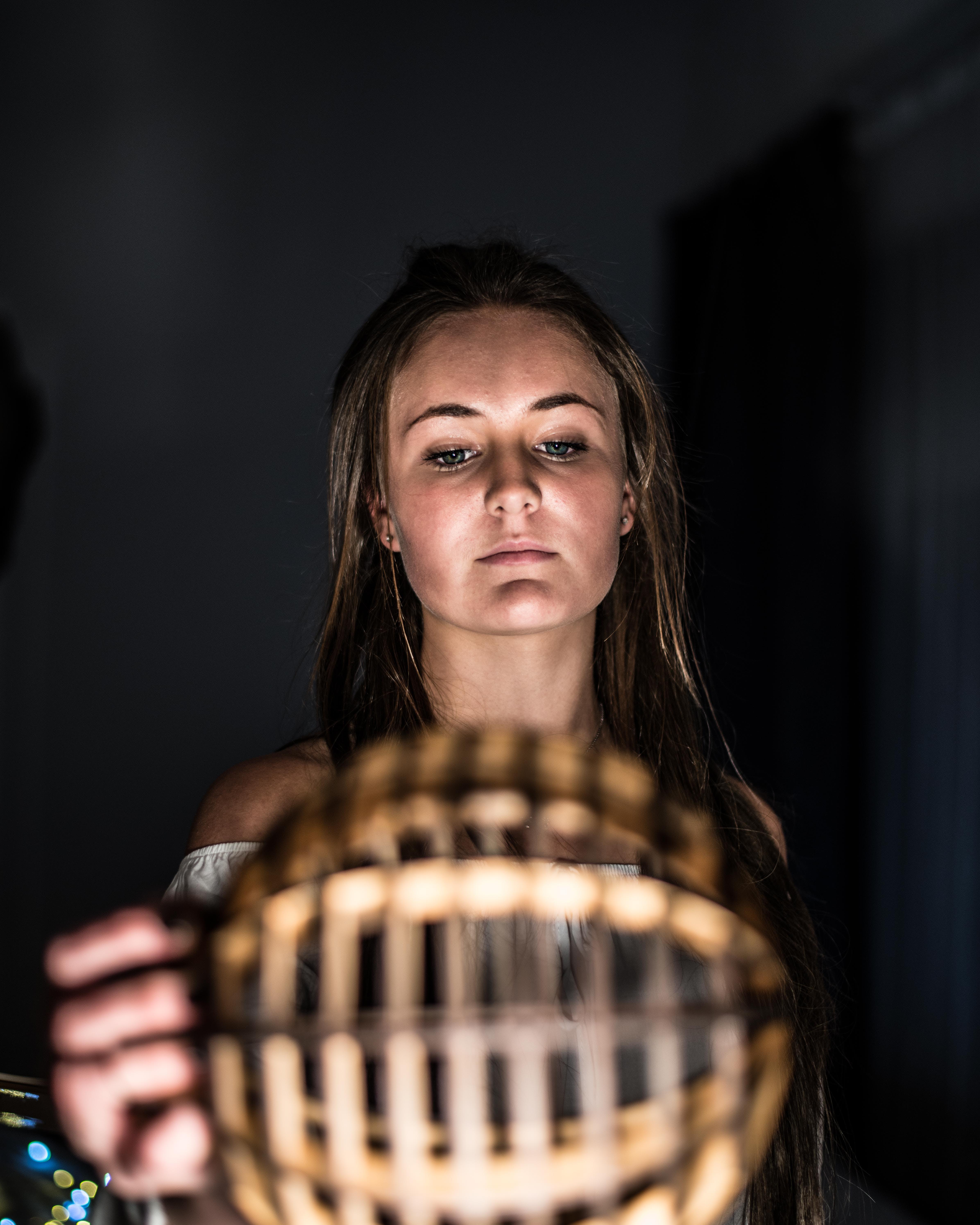 Woman Holding Brown Wooden Ball Inside Deemed Room