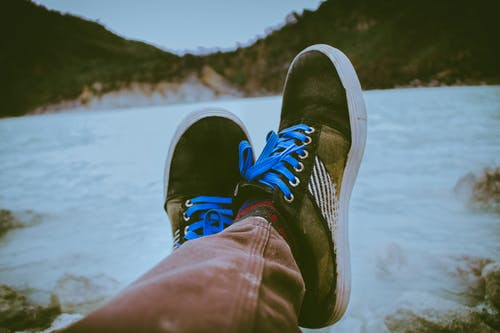 Person Wearing Black and Brown Shoes in Front of Body of Water