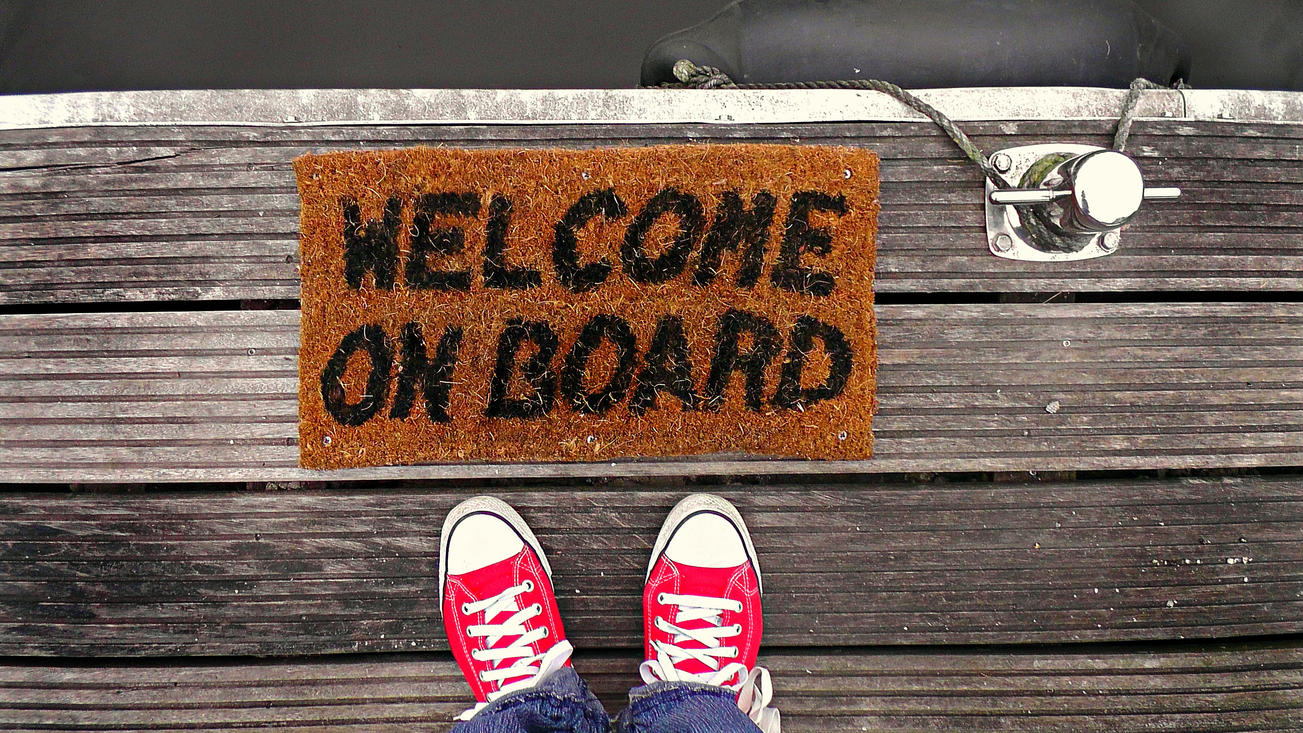 Red sneakers and welcome mat with the words Welcome on Board