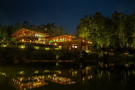 Brown House With Yellow and Red Light Near Green Tree and Body of Water during Nighttime