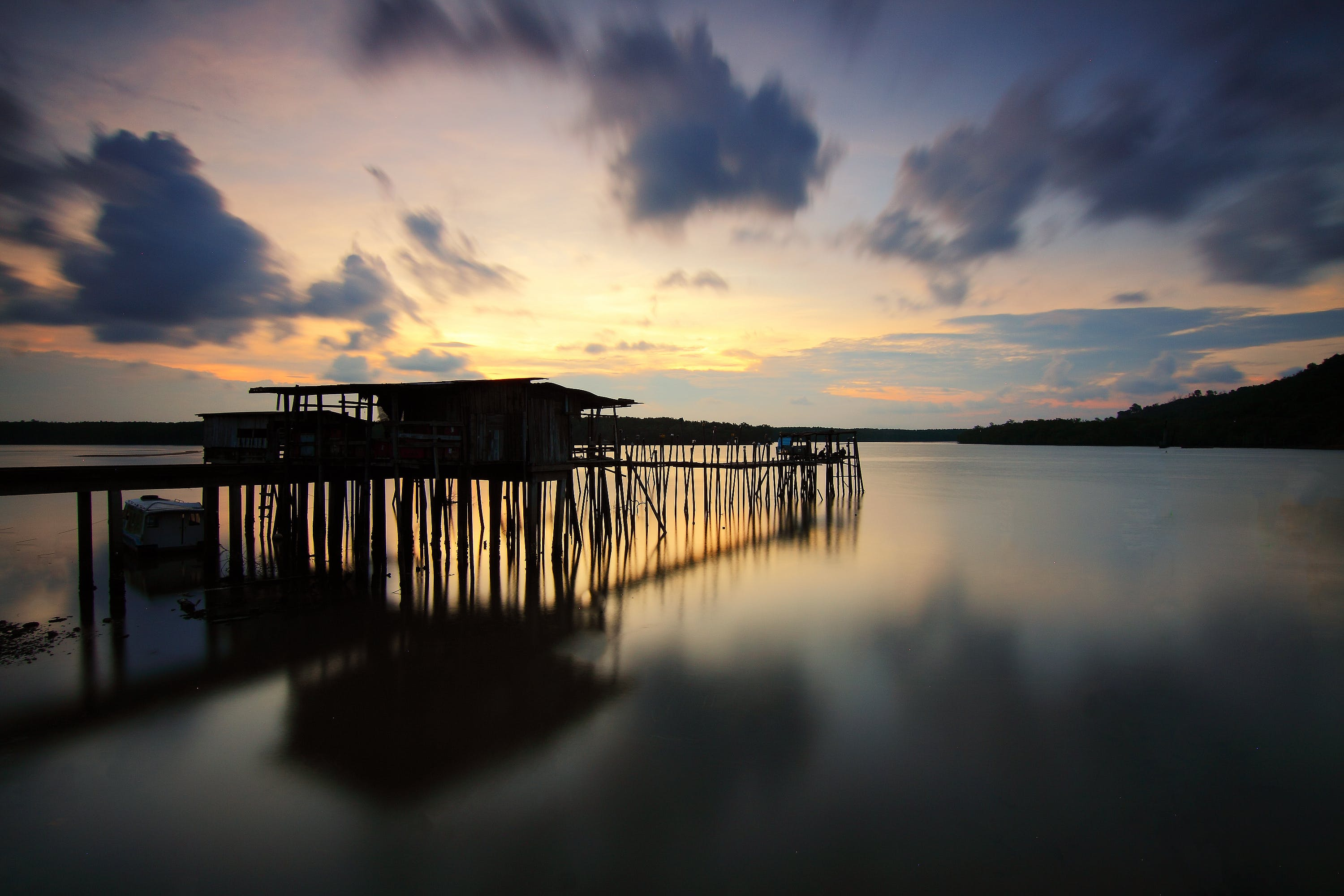Silhouette of Wooden House and Walkbridge on Water