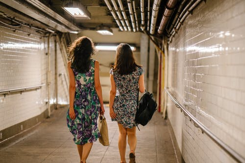 Two Women Carrying Bags While Walking in Tunnel