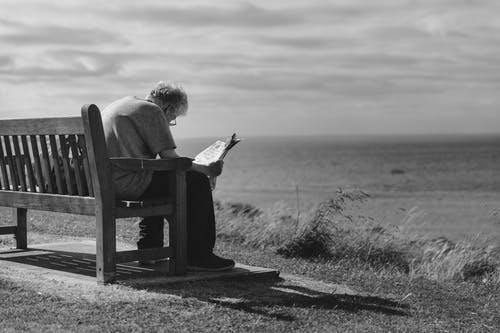 Grayscale Photo of Man Sitting on Brown Wooden Bench Reading News Paper during Day Time