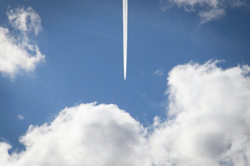 Low-angle Photography of White Contrail Beside White Clouds Under Blue Sky