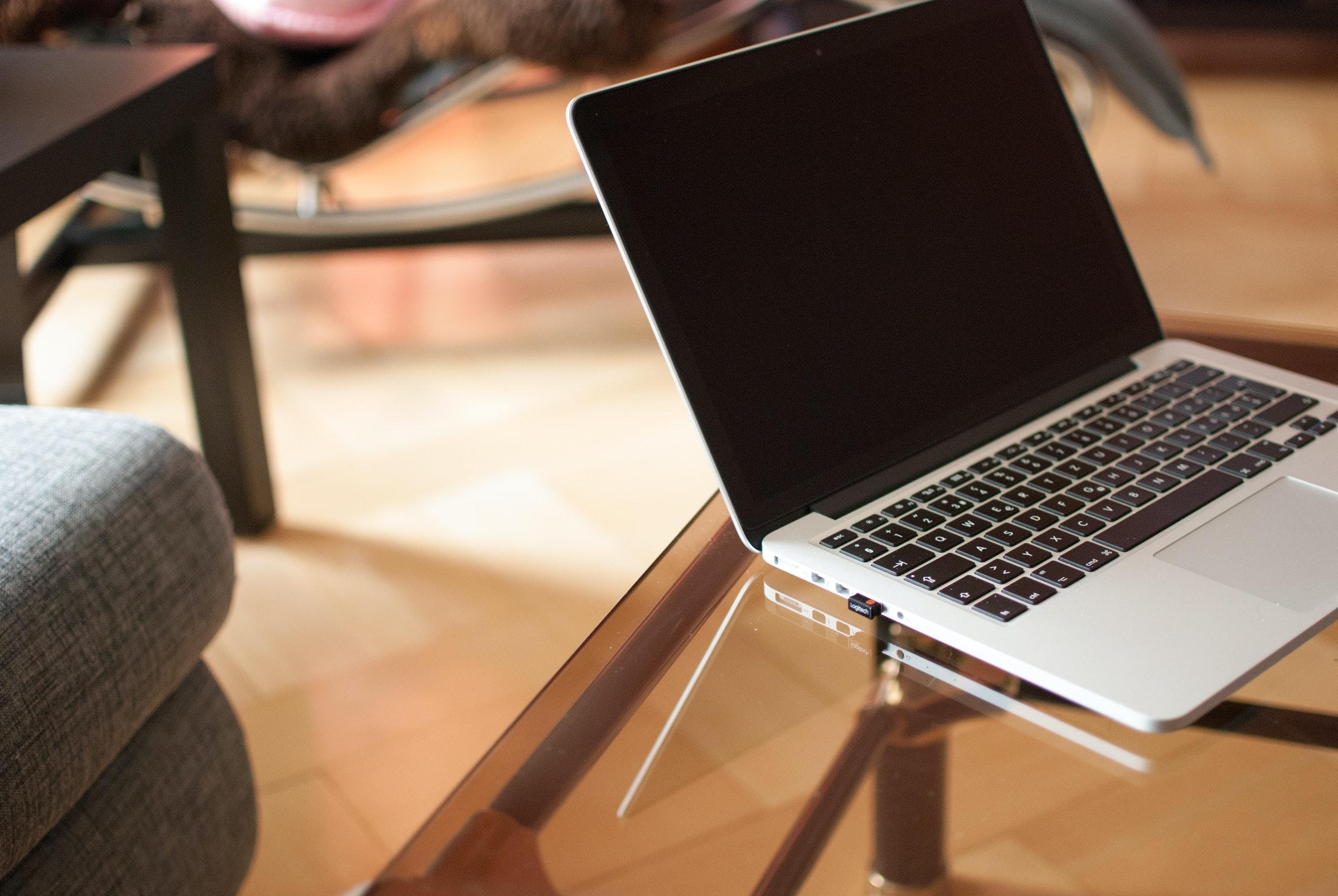macbook pro with black screen beside notebook on brown. Black Bedroom Furniture Sets. Home Design Ideas