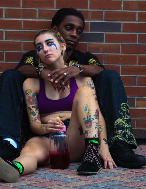 Woman And Man Sitting On Ground While Leaning On Wall