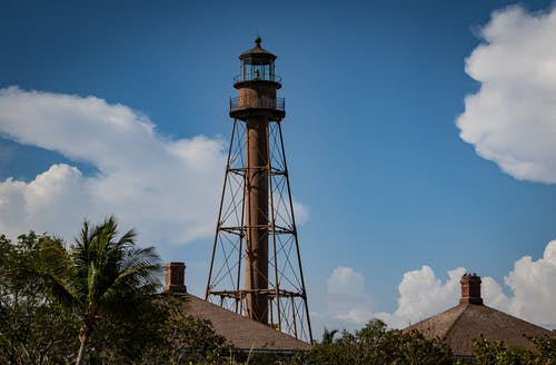 Brown Lighthouse Under Cloudy Sky
