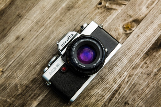 Black and Gray Minolta Dslr Camera on Top of Brown Wooden Surface