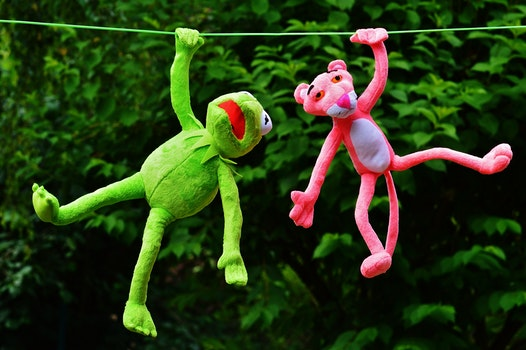 Shallow Focus Photography of Pink Panther and Kermit the Frog Plush Toy