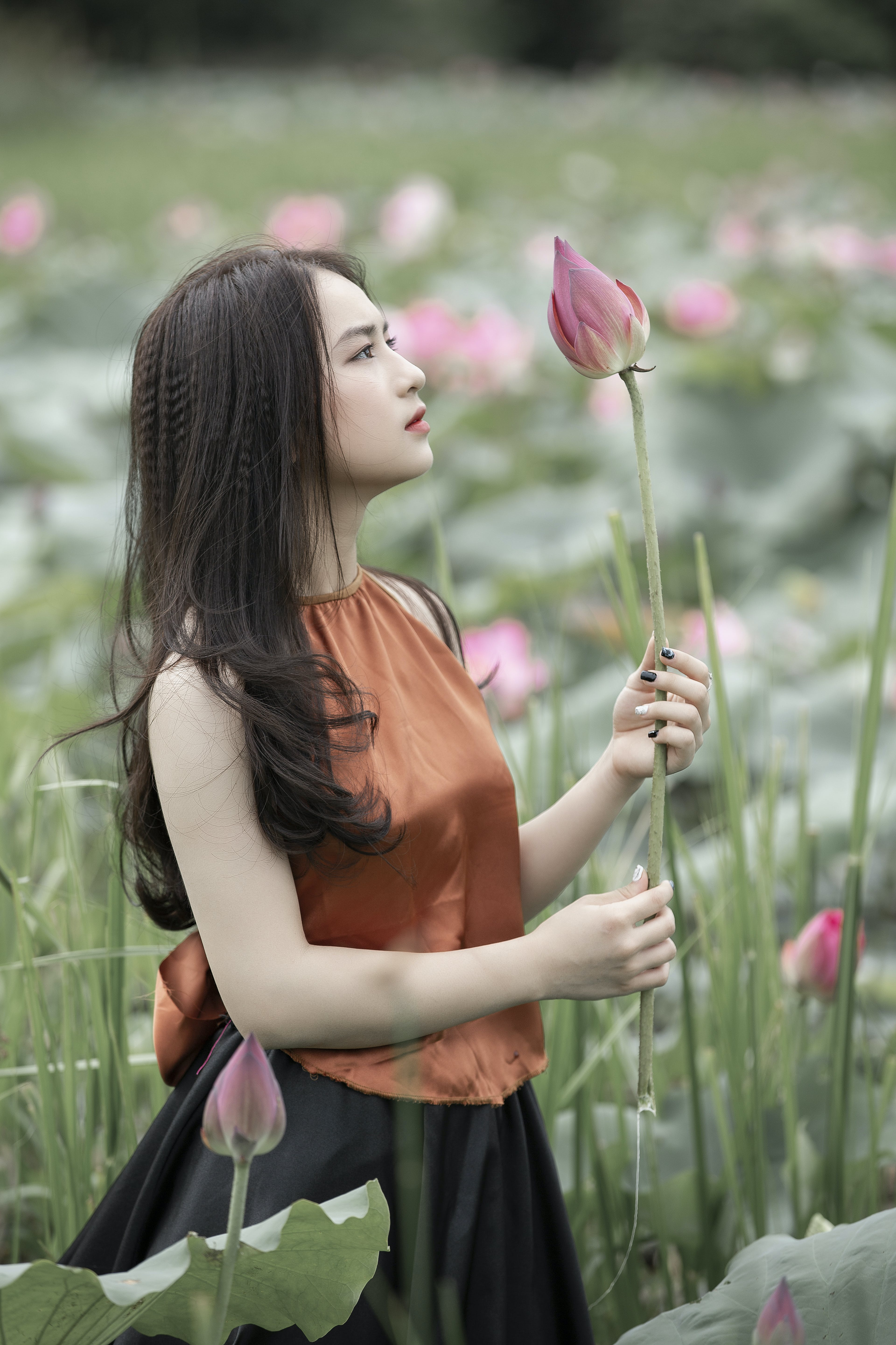 Woman in Brown Shirt Holding Pink Petaled Flower