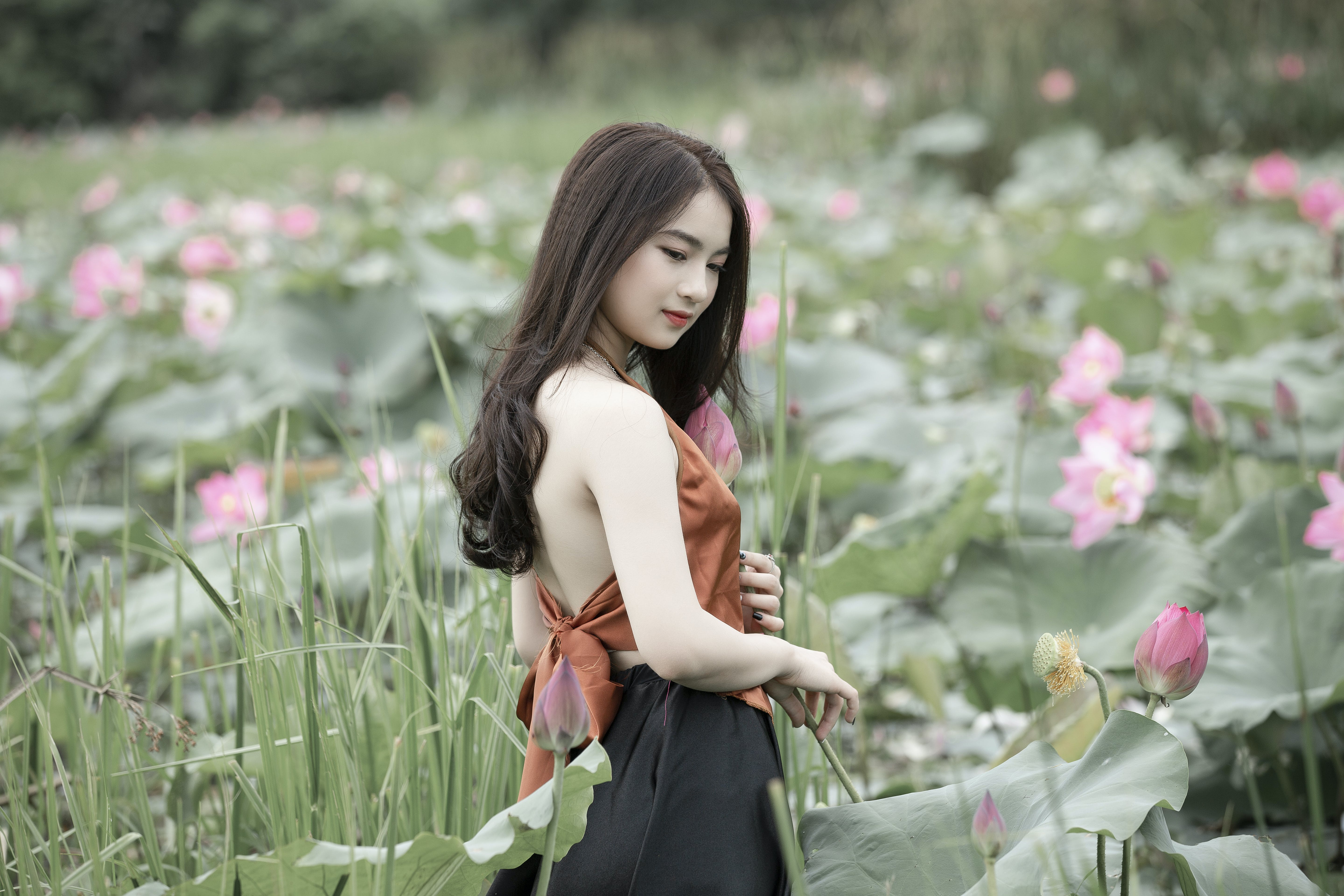 Woman Wearing Brown Top and Black Skirt in the Middle of Flower Field