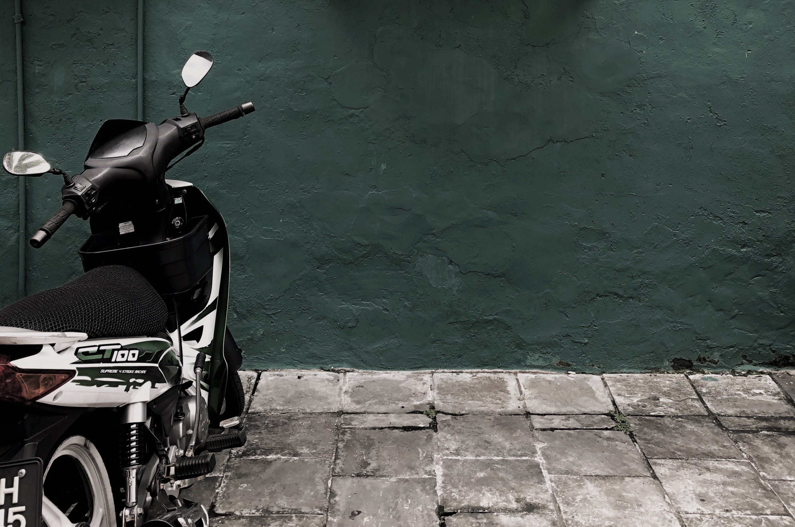 Black and White Ct 100 Motorcycle Parked Near Concrete Wall