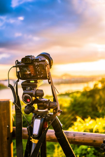 Selective focus photo of dslr camera with tripod stabilizer