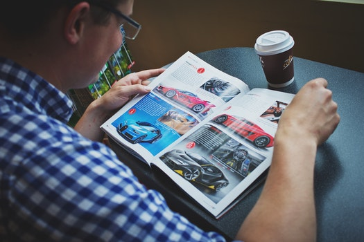 Man in Blue and White Gingham Print Shirt Reading Car Magazine