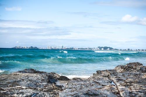 Бесплатное стоковое фото с вода, волны, голубая вода, каменистый берег