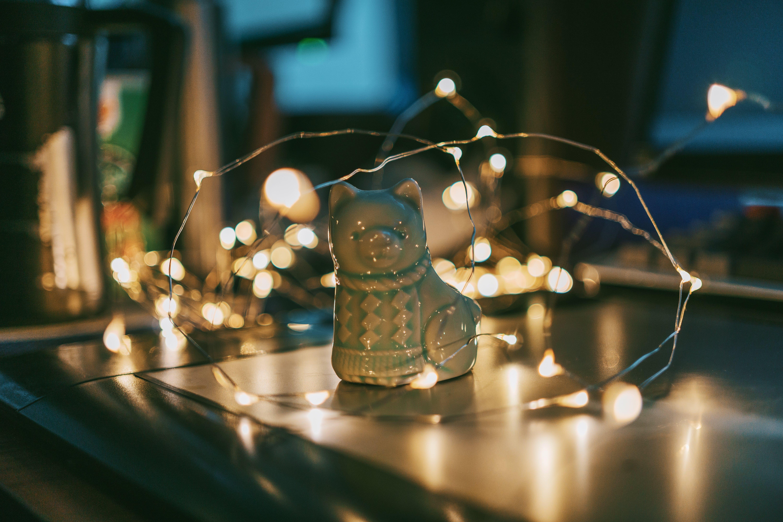 Close-up Photo of Gray Ceramic Cat Figurine Near String Lights
