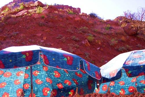 Kostenloses Stock Foto zu regenschirm, roter stein, sand