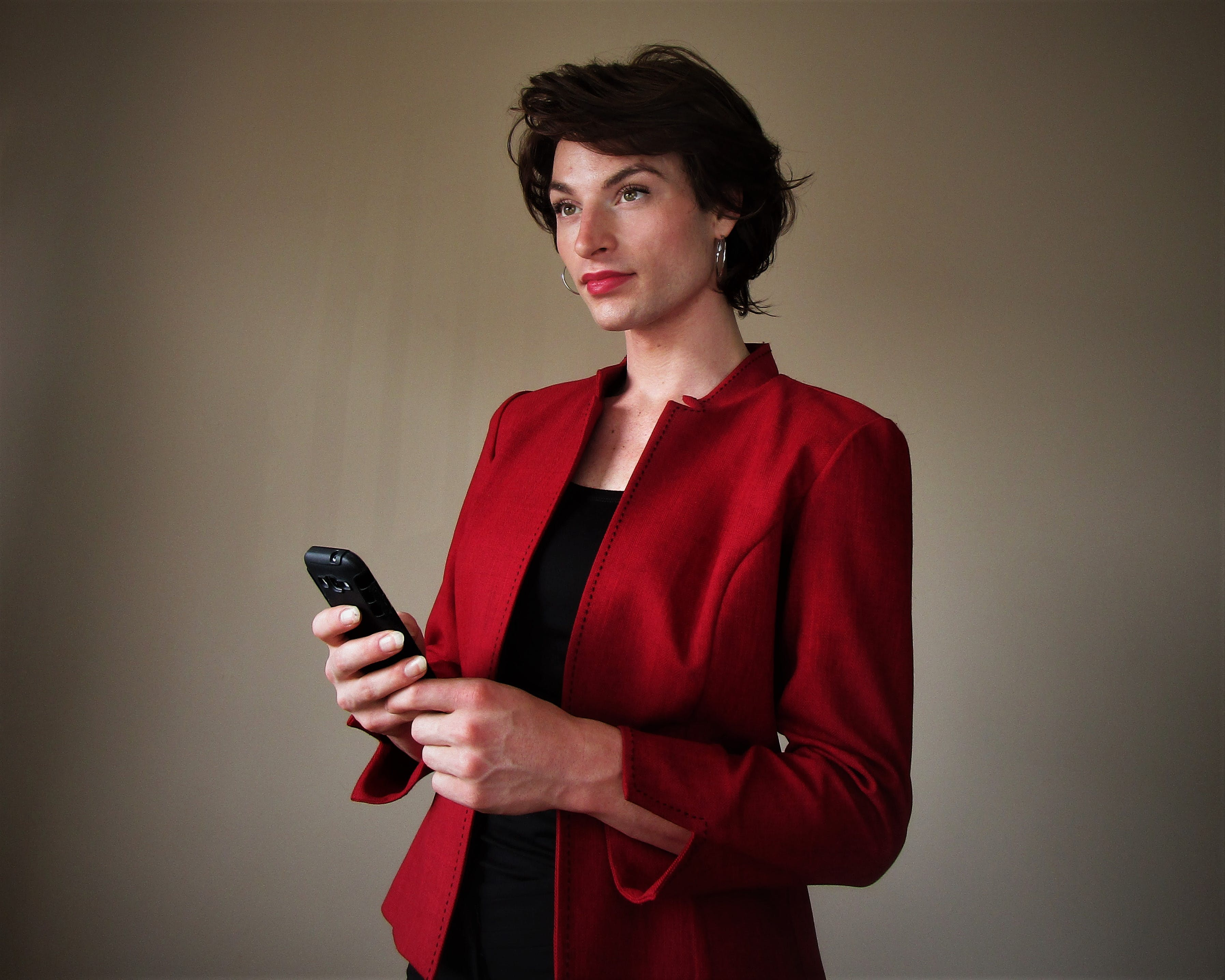 Woman Wearing Red Blazer Holding Smartphone